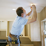 photo of electrician fitting a kitchen spotlight